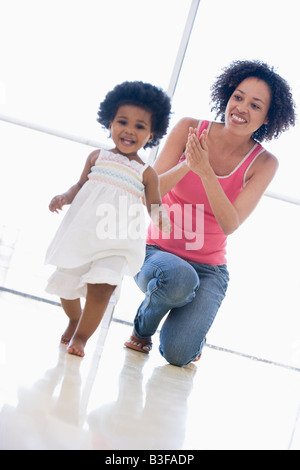 Mother and daughter indoors playing and smiling - Stockfoto