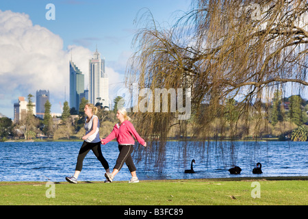 Two women exercising in a park with skyscrapers in the distance. Lake Monger, Perth, Western Australia - Stock Photo