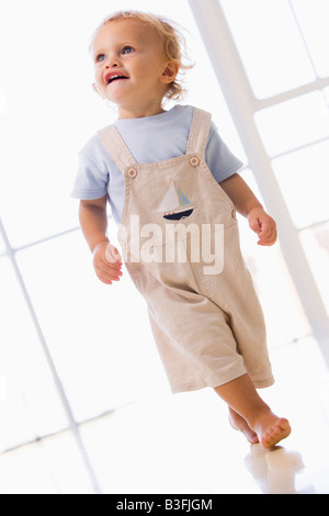 Young boy walking indoors smiling - Stockfoto