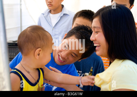 Hmong mom and dad cheer son after being treated in health care tent. Hmong Sports Festival McMurray Field St Paul - Stock Photo