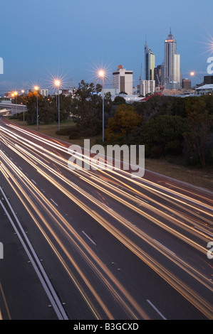 Light trails along the Mitchell Freeway heading north, with the city of Perth, Western Australia, in the background - Stock Photo