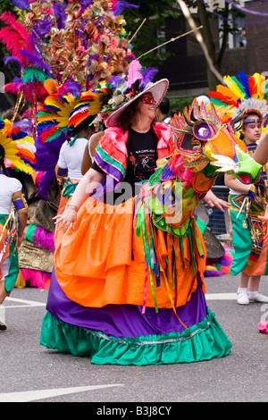 Notting Hill Carnival Parade, schöne lachende Reife weiße Dame in exotischen bunten Kostüm orange lila & grüne Pferd - Stockfoto
