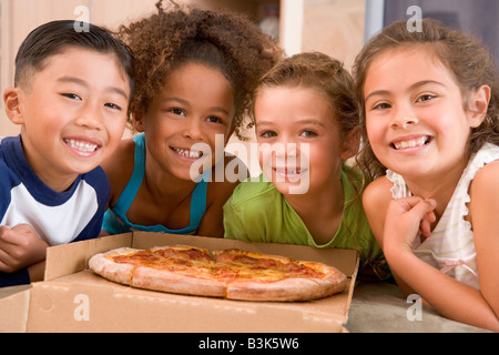 Four young children indoors with pizza smiling - Stock Photo