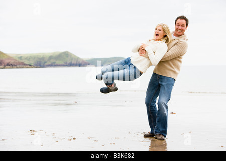 Couple playing on beach smiling - Stock Photo