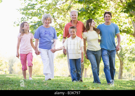 Extended family walking in park holding hands and smiling - Stock Photo