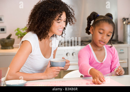 Woman and young girl in kitchen with art project smiling - Stock Photo