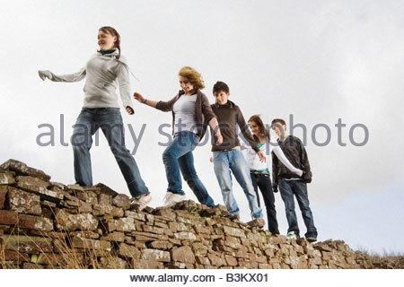Teenage friends walking along rock wall - Stock Photo
