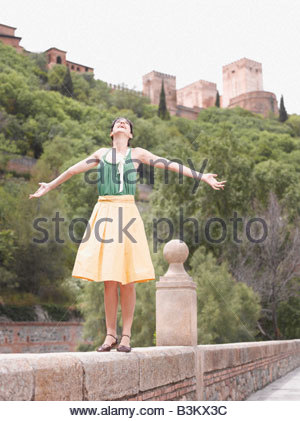 Woman standing on wall with arms outstretched - Stock Photo
