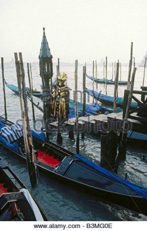 Costumed man and gondolas in Venice, Italy - Stock Photo