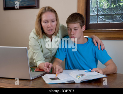 A mother helps her teen-aged son with his school homework with a laptop open, perhaps using the internet as a tool. - Stock Photo