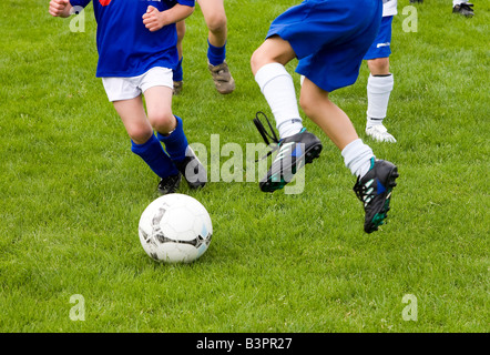 Close-up of players fighting for the ball in a soccer game for children - Stock Photo