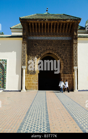 Two children leave through the entrance to the Mausoleum of Moulay Ismail in Meknes, Morocco. - Stock Photo
