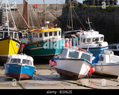 Fishing boats in Newquay Harbour at low tide - Stock Photo