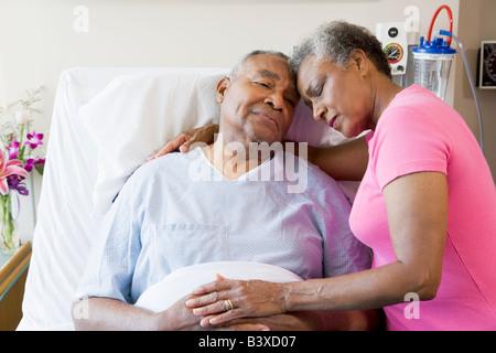 Senior Couple Embracing In Hospital - Stock Photo