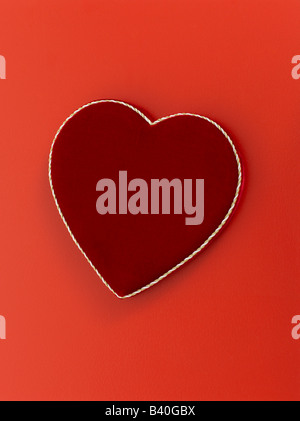 Heart shaped valentines day chocolate box on red background - Stock Photo