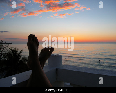 Man with feet propped up enjoying the brilliant sunset over the Caribbean on Negril beach Jamaica - Stock Photo