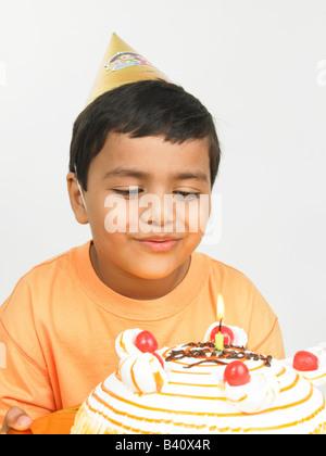 asian boy of indian origin with his birthday cake wearing orange tee shirt, smiling - Stock Photo