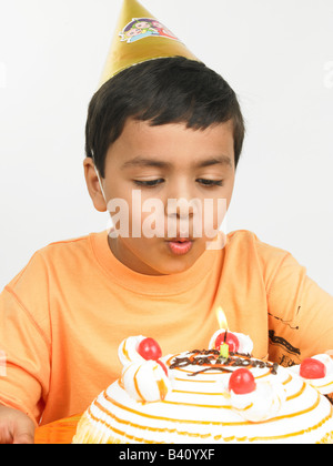 asian boy of indian origin blowing the candle on his birthday cake - Stock Photo