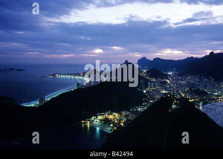 View of Rio de Janeiro with its distinctive skyline of hills and Copacabana Beach from atop Sugar Loaf at sunset - Stock Photo