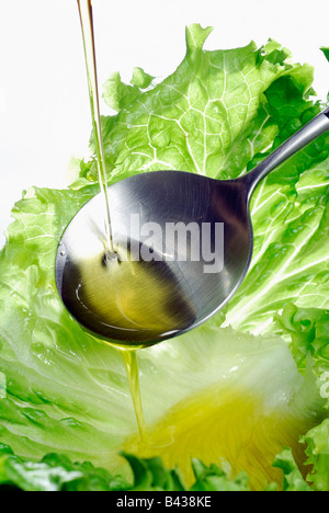 Pouring a drop of olive oil onto a lettuce leaf - Stock Photo