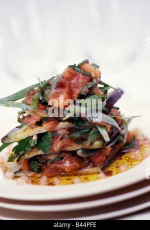Eggplant mille-feuille with crushed tomatoes and fresh herbs - Stock Photo