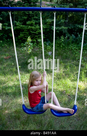 A young girl rests on a white bench swing and plays on swings in a green field during a family vacation in the utah - Stockfoto
