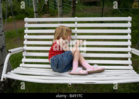 A young girl rests on a white bench swing and plays on swings in a green field during a family vacation in the utah - Stock Photo