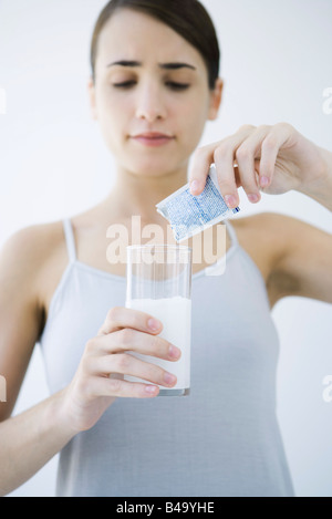 Woman pouring effervescent medicine into glass of water - Stockfoto