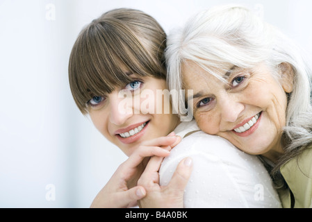 Senior woman leaning against adult daughter's back, both smiling at camera and holding hands - Stock Photo