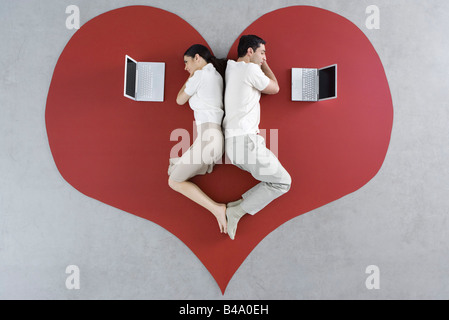 Man and woman lying back to back on large heart, both looking at laptop computers - Stock Photo