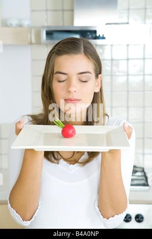 Frau, Augen geschlossen, Platte mit einzelnen rohen Rettich in Mitte zu präsentieren - Stockfoto