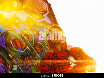 Man in front of graffiti - Stock Photo