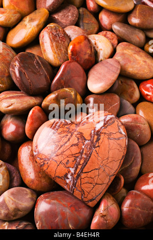 Heart shaped stone on bed of other rocks - Stock Photo