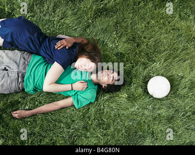 A young couple lying in the grass sleeping - Stock Photo