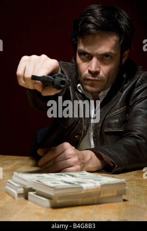 A man holding a gun threateningly - Stock Photo