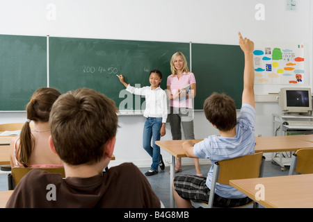 A teacher and a student at the blackboard, facing the class - Stock Photo
