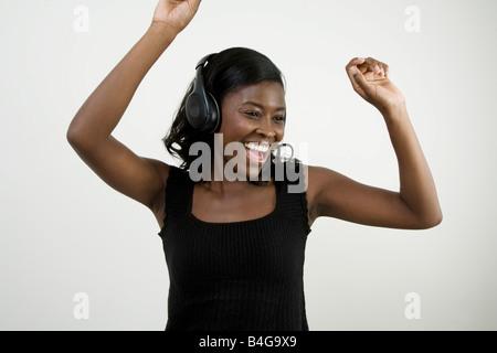 An African American woman wearing headphones and dancing, studio shot - Stock Photo