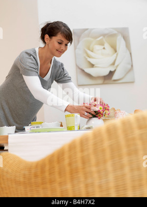 Young woman arranging flowers in vase on table - Stock Photo