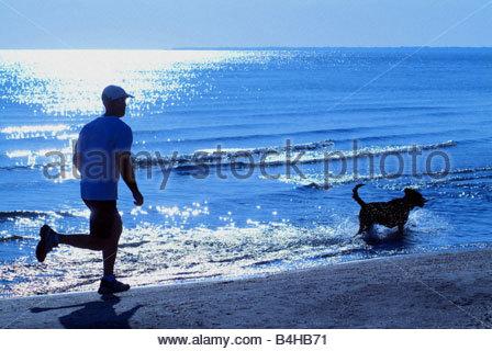 Man and dog running on beach - Stock Photo