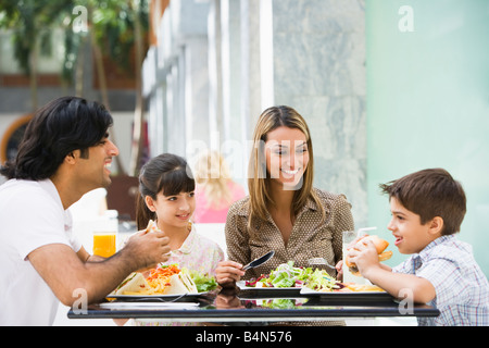 Family at restaurant eating and smiling (selective focus) - Stock Photo