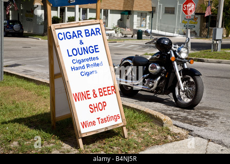 Motorcycle by a Cigar bar sign in small town America - Stock Photo