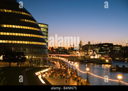 South Bank Thames Path at dusk with New City Hall and HMS Belfast viewed from Tower Bridge London UK - Stock Photo