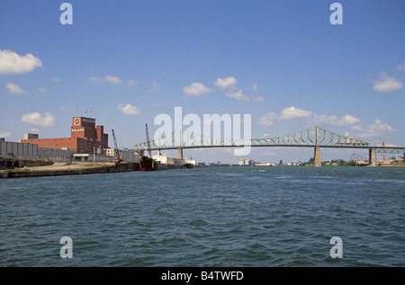 Factories and ships along the St Lawrence River and St Lawrence Seaway in the Old Town section of Montreal Canada - Stock Photo