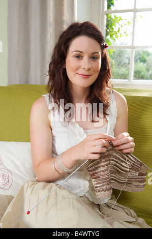 Young woman knitting on couch - Stock Photo
