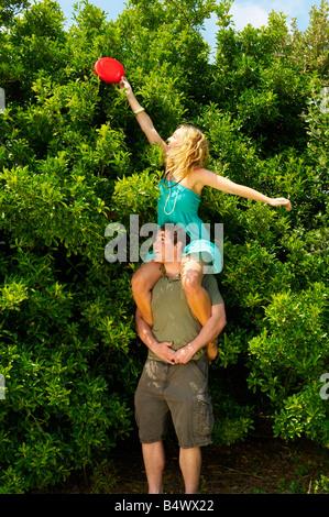 http://n450v.alamy.com/450v/b4wx22/woman-sitting-on-mans-shoulders-holding-b4wx22.jpg
