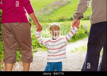 Senior couple walking with child - Stock Photo