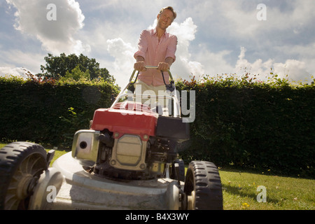 Man with push lawnmower, low angle - Stock Photo