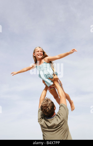 Father lifting daughter in air - Stockfoto