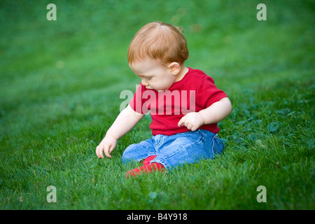 Young redheaded baby boy sitting outside on grass - Stock Photo