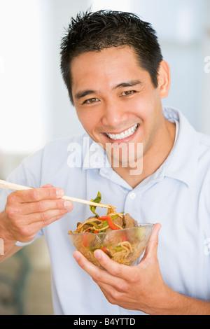 Man Enjoying Chinese Food With Chopsticks - Stockfoto